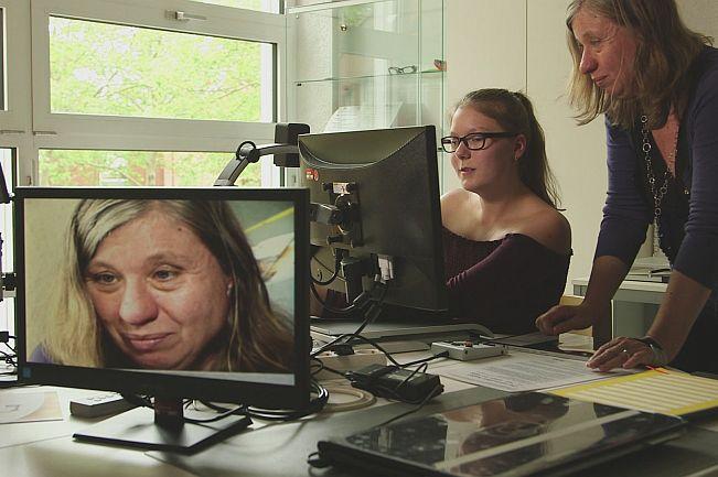 Lehrerin mit Schülerin vor einem Vergrößerungsbildschirm mit Blick wie groß das Angezeigte auf einem anderem PC aussieht