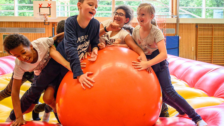 Einige Kinder auf einer Luftmatratze spielen mit einem orangenen Gymnastikball