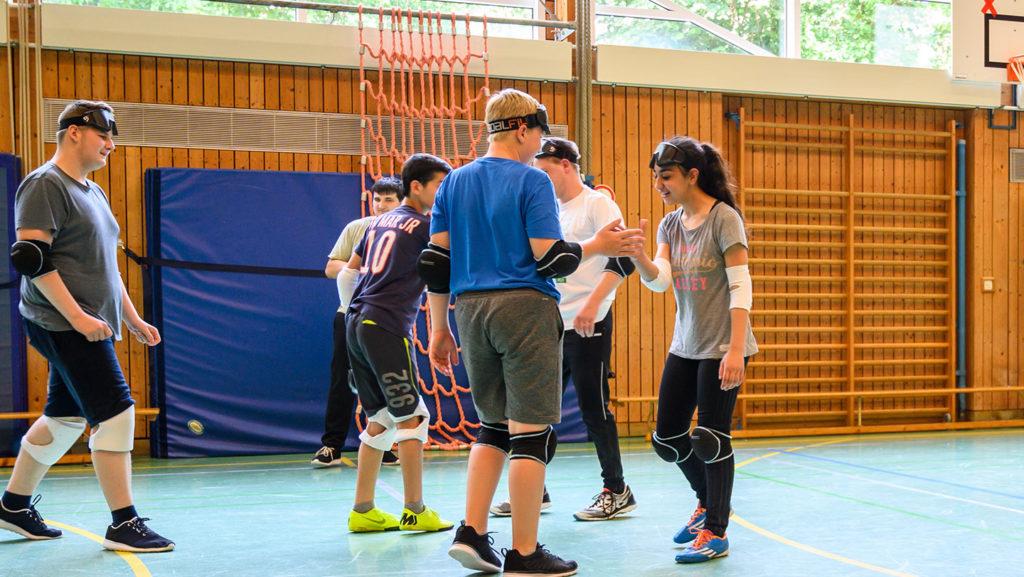 Schüler in der Sporthalemit Knie und Elenbogenschoner beim Goalballspielal