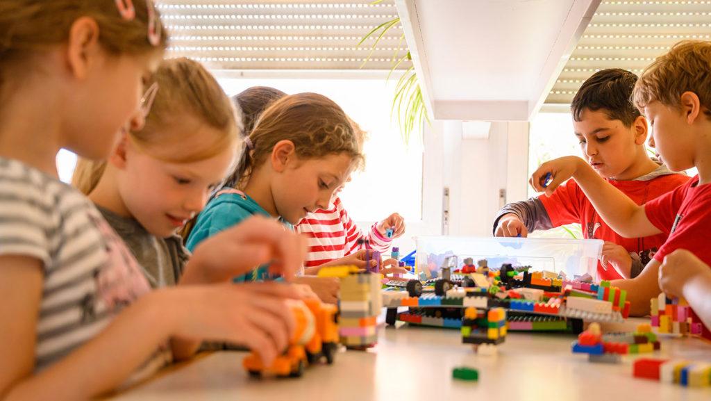 Die Kinder spielen am Tisch mit Legosteinen