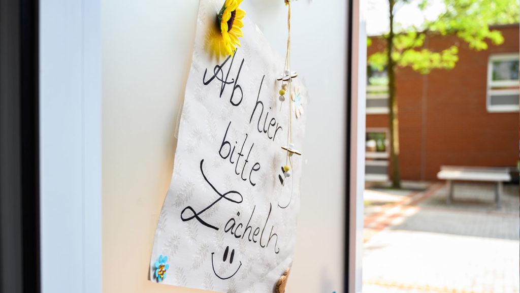 """Auf der Internatwand hängt ein Plakat mit der Aufschrift: """"Ab hier bitte Lächeln"""""""
