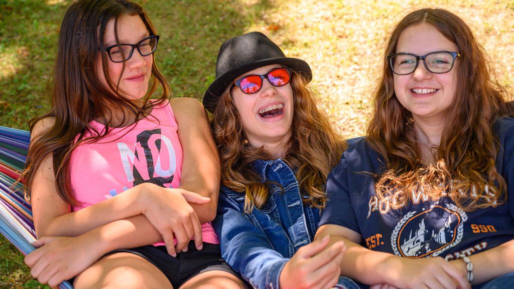 Drei fröhliche Mädchen sitzen gemeinsam auf einer Hängematte