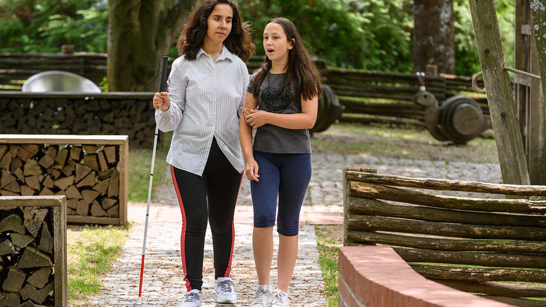 Zwei Schülerinnen unterhalten sich und spazieren duch den Park. Eine davon mit Blindenstock.