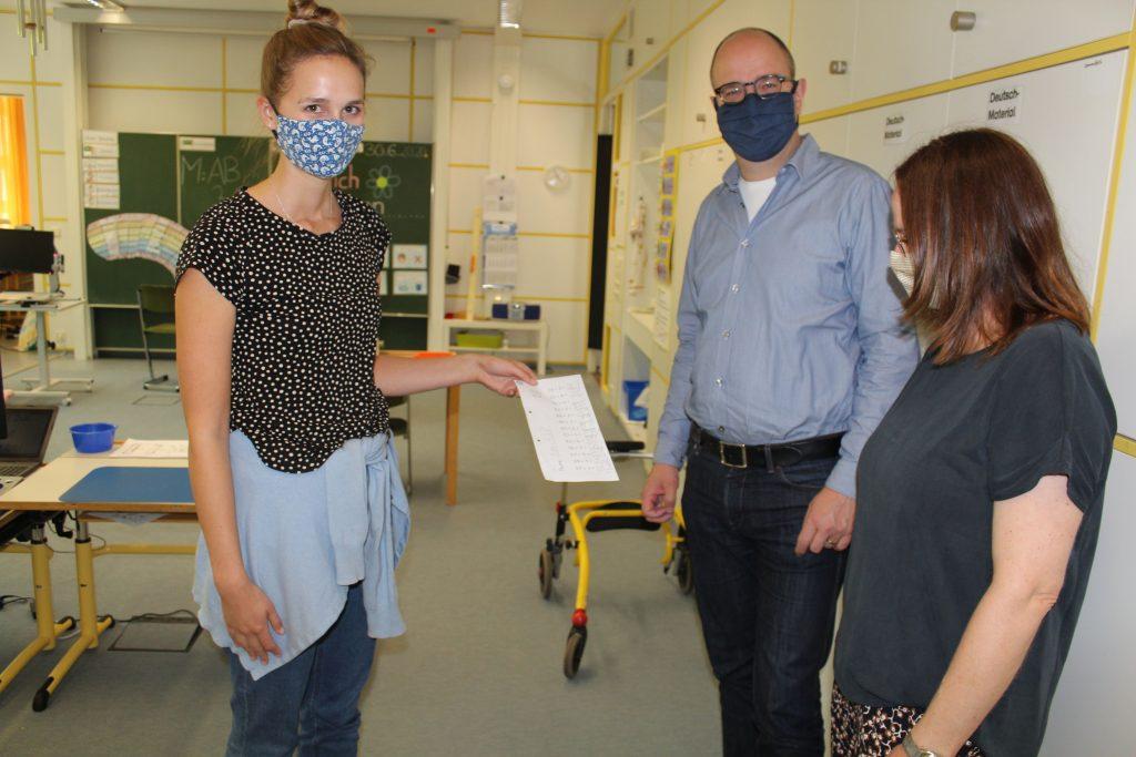 Frau Reinhard zeigt Frau Keller und Herrn Jeske Danielas schulische Fortschritte.